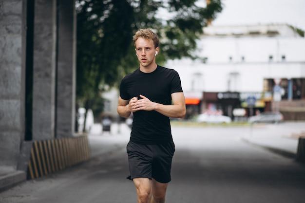 Giovane uomo che corre in città al mattino