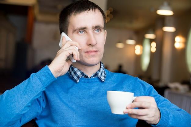 Giovane uomo che fa chiamata a colazione