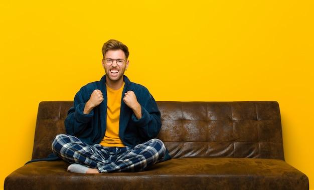 Giovane uomo che indossa il pigiama urlando trionfante, ridendo e sentendosi felice ed eccitato mentre celebra il successo. seduto su un divano