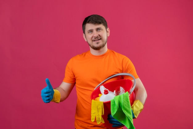 Giovane uomo che indossa maglietta arancione e guanti di gomma che tiene secchio con strumenti di pulizia guardando fiducioso sorridente positivo e felice che mostra i pollici in su in piedi sopra il muro rosa