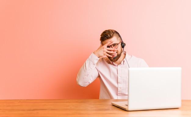 Giovane uomo che lavora in un call center lampeggia attraverso le dita, imbarazzato volto che copre.