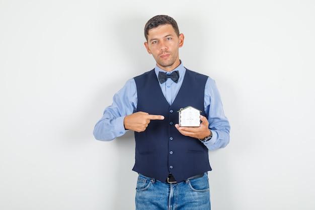 Giovane uomo che punta il dito al modello di casa in tuta, jeans