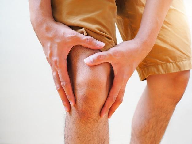 Giovane uomo che soffre di artrosi dolore al ginocchio, dolore di corpo e gambe per la gotta.