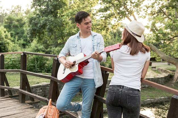 Giovane uomo che suona la chitarra alla sua ragazza
