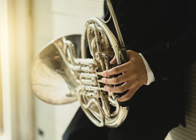Giovane uomo che suona musica classica corno francese