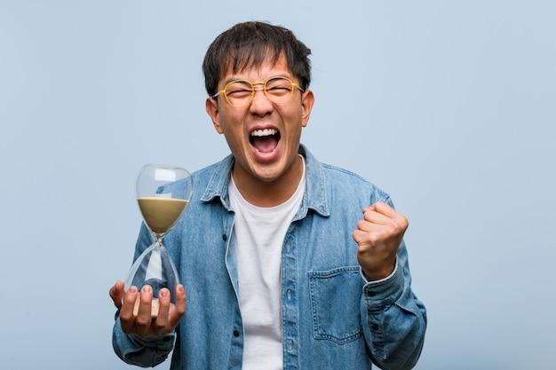 Giovane uomo cinese che giudica un temporizzatore della sabbia sorpreso e colpito