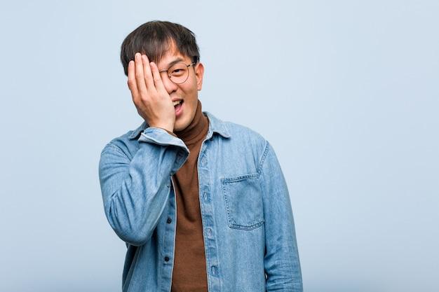 Giovane uomo cinese che grida felice e che copre il viso con la mano