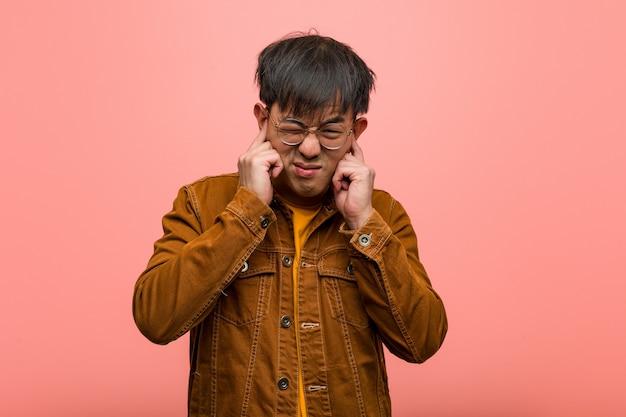Giovane uomo cinese che indossa una giacca che copre le orecchie con le mani