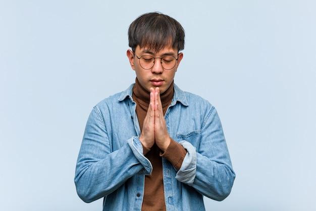 Giovane uomo cinese che prega molto felice e sicuro