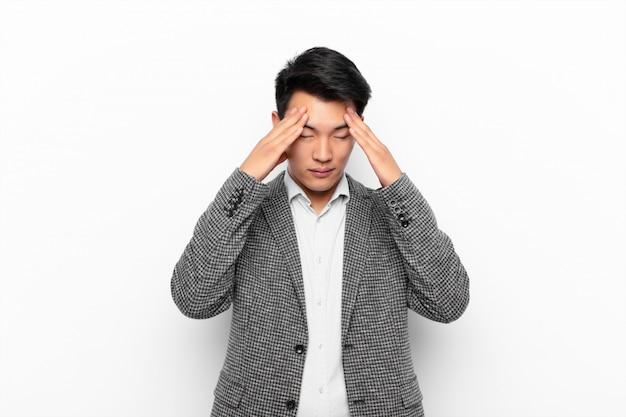 Giovane uomo cinese che sembra stressato e frustrato, che lavora sotto pressione con un mal di testa e turbato da problemi contro la parete di colore piatto