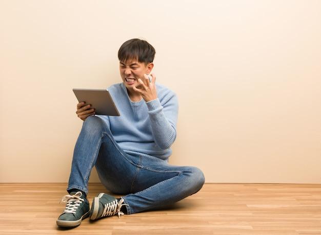 Giovane uomo cinese che si siede facendo uso della sua compressa arrabbiata e turbata