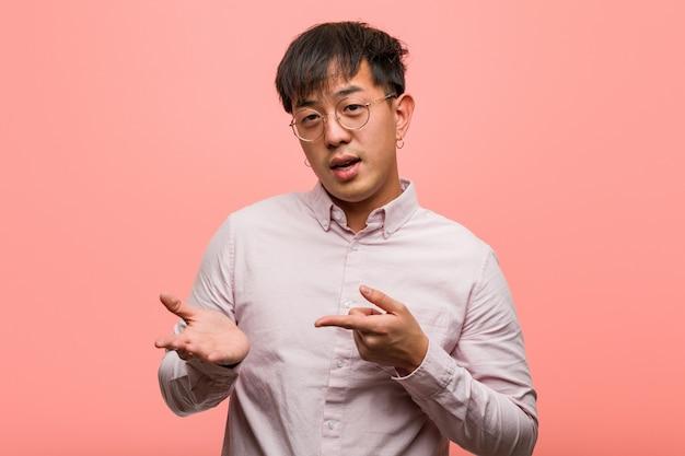 Giovane uomo cinese che tiene qualcosa con la mano