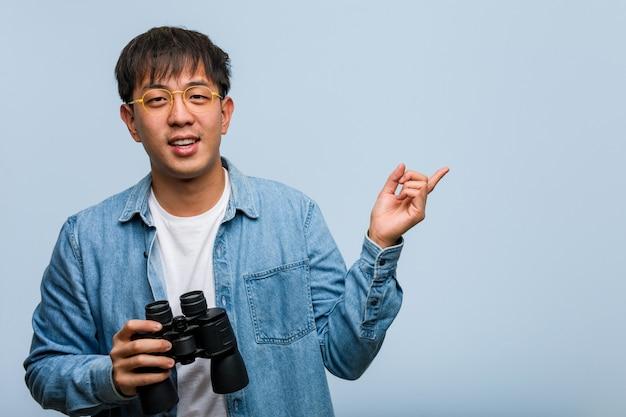 Giovane uomo cinese che tiene un binocolo che indica il lato con il dito