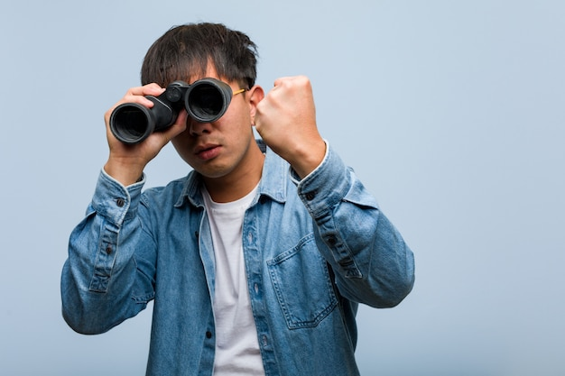 Giovane uomo cinese che tiene un binocolo che mostra pugno alla fronte, espressione arrabbiata