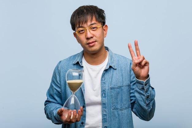 Giovane uomo cinese che tiene un temporizzatore della sabbia che mostra numero due