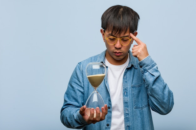 Giovane uomo cinese che tiene un temporizzatore della sabbia che pensa ad un'idea