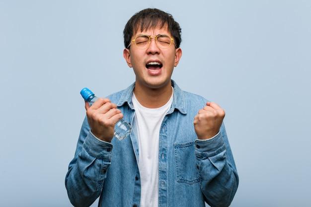 Giovane uomo cinese che tiene una bottiglia d'acqua sorpreso e scioccato