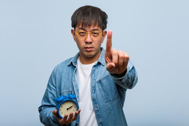 Giovane uomo cinese che tiene una sveglia che mostra il numero uno