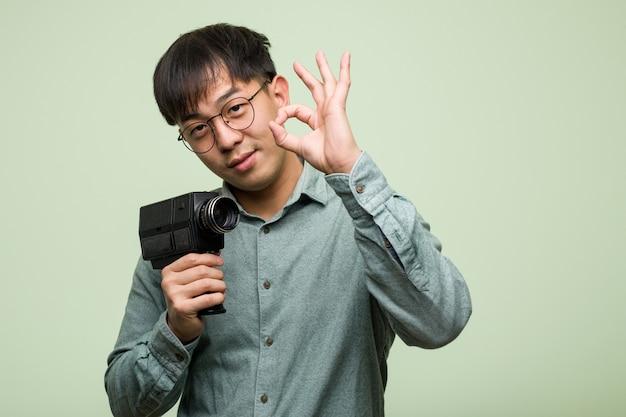 Giovane uomo cinese che tiene una videocamera d'annata allegra e sicura che fa gesto giusto