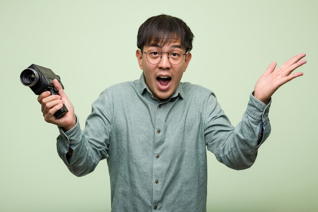 Giovane uomo cinese che tiene una videocamera d'annata che celebra una vittoria o un successo