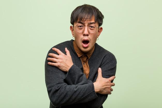 Giovane uomo cinese contro una parete verde