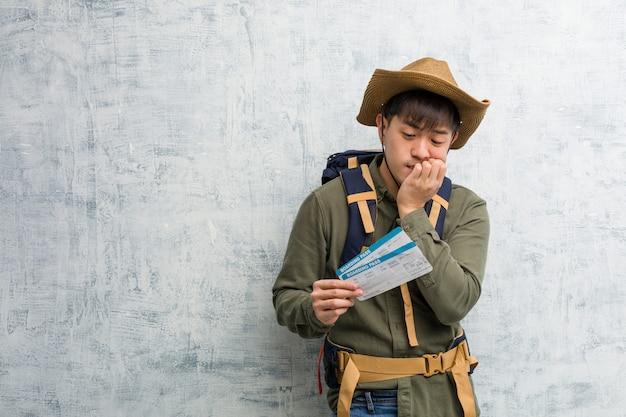Giovane uomo cinese di esplorazione che tiene un biglietto aereo che morde le unghie, nervoso e molto ansioso