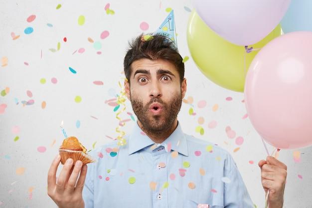 Giovane uomo circondato da coriandoli che tengono cupcake e palloncini
