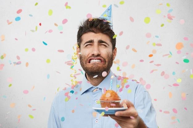 Giovane uomo circondato da coriandoli tenendo cupcake