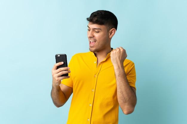 Giovane uomo colombiano utilizzando il telefono cellulare isolato sul blu che celebra una vittoria
