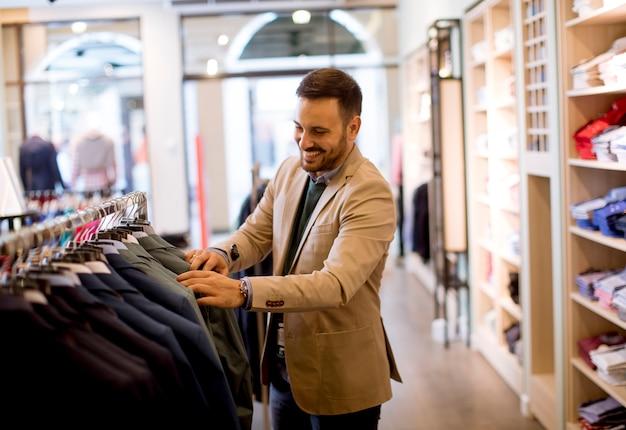 Giovane uomo comprare vestiti nel negozio