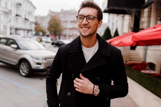 Giovane uomo con gli occhiali che indossano abiti autunnali camminando per strada ragazzo elegante con acconciatura moderna in strada urbana.