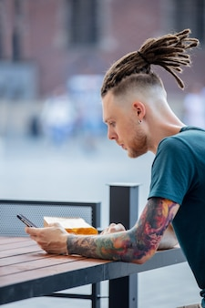 Giovane uomo con il telefono è seduto al tavolo in un caffè della città