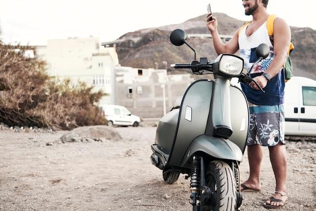 Giovane uomo con la moto messaggistica con il telefono