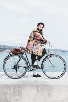 Giovane uomo con la sua bicicletta sul frangiflutti vicino alla costa