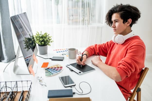 Giovane uomo con le cuffie guardando lo schermo del computer mentre si utilizza la tavoletta grafica e lo stilo per ritoccare le foto