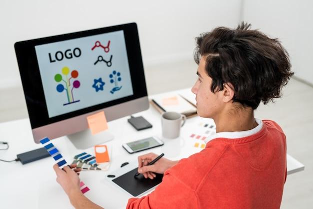 Giovane uomo con tavolozza dei colori creando logo per sito web mentre era seduto davanti al computer e utilizzando la tavoletta grafica