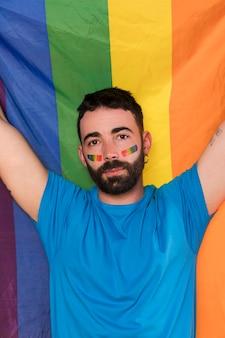 Giovane uomo contro la bandiera arcobaleno