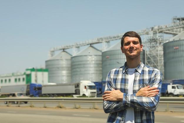 Giovane uomo contro silos di grano. affari agricoli
