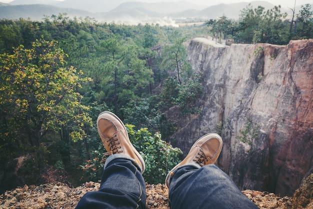 Giovane uomo coraggioso seduto su un grande grand canyon