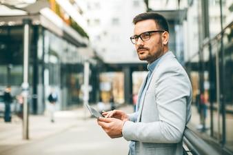 Giovane uomo d'affari bello con la compressa digitale dall'edificio per uffici