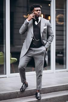 Giovane uomo d'affari africano che per mezzo del telefono