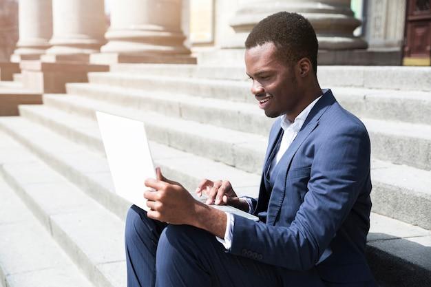 Giovane uomo d'affari africano che si siede sui punti facendo uso del computer portatile a all'aperto