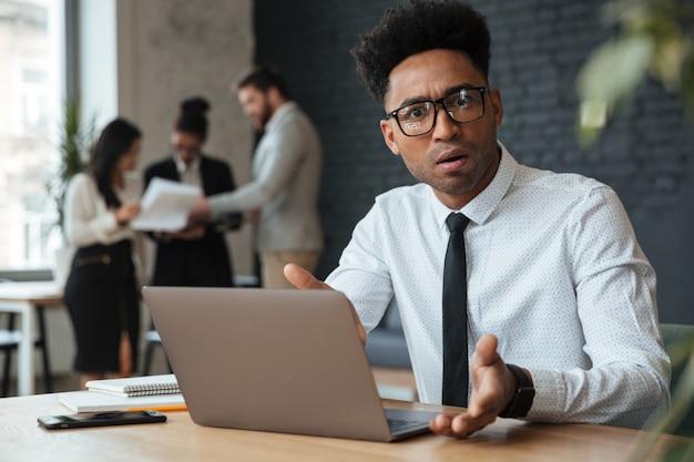 Giovane uomo d'affari africano confuso