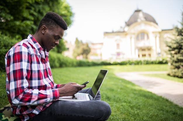Giovane uomo d'affari afroamericano attraente con il computer portatile che si siede sull'erba e parla al cellulare nel parco