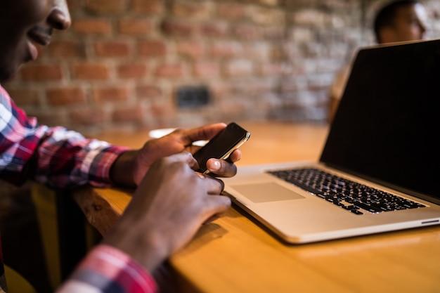 Giovane uomo d'affari afroamericano attraente con occhiali e laptop seduto nel bar caffetteria e utilizzare il telefono cellulare.
