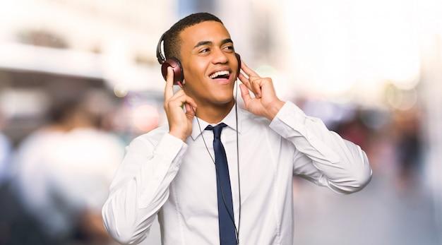 Giovane uomo d'affari afroamericano che ascolta la musica con le cuffie nella città