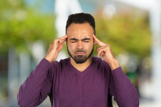 Giovane uomo d'affari afroamericano che soffre di mal di testa dopo una dura giornata di lavoro