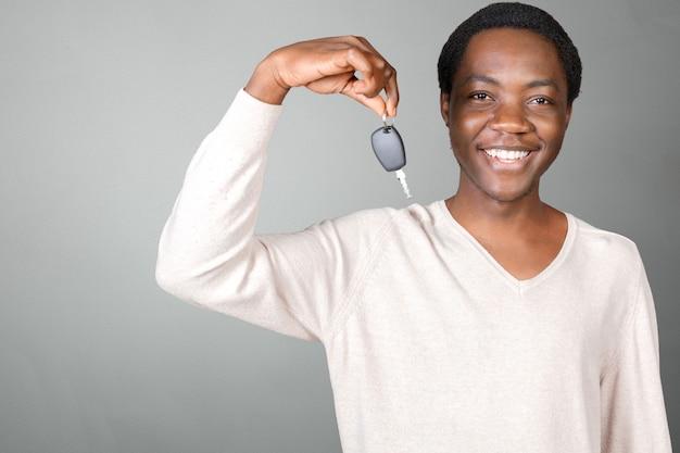 Giovane uomo d'affari afroamericano che tiene una chiave dell'automobile