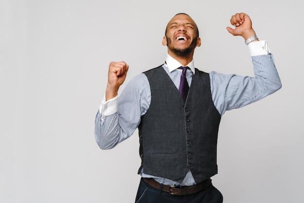 Giovane uomo d'affari afroamericano gridante astuto che fa gesto della vittoria di successo.