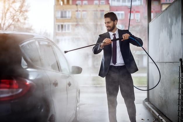 Giovane uomo d'affari alla moda allegro felice in vestito che lava la sua automobile alla stazione di self service di lavaggio manuale dell'automobile.